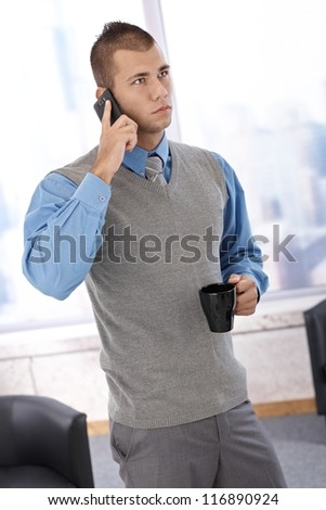 Businessman standing in office with coffee cup handheld, listening to mobile phone conversation, concentrating. - stock photo