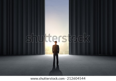 businessman standing in room with big curtains - stock photo