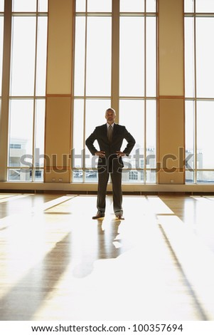 Businessman standing in sunlit room with hands on his hips
