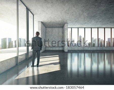 Businessman standing in sunny office - stock photo