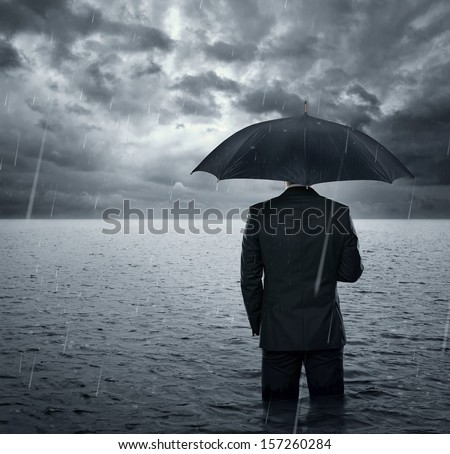 Businessman standing in the dramatic ocean before storm  - stock photo