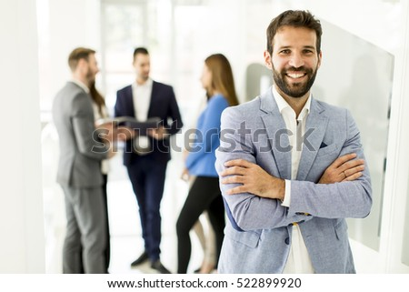 Businessman standing in the office and other young business people talking in  background