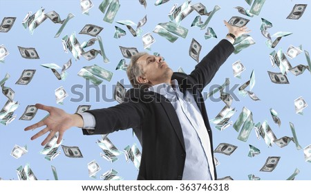 Businessman standing in the rain of money dollar bills