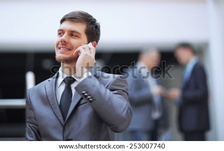 businessman standing inside modern office building talking on a mobile phone - stock photo