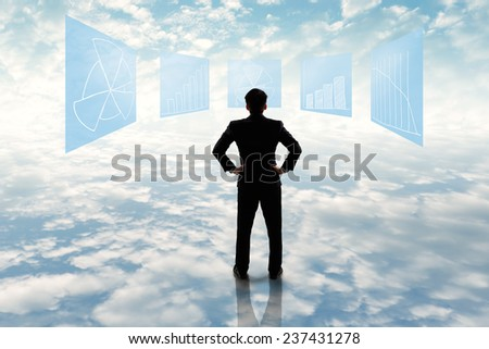 Businessman standing looking at business flowchart in cloudy setting - stock photo