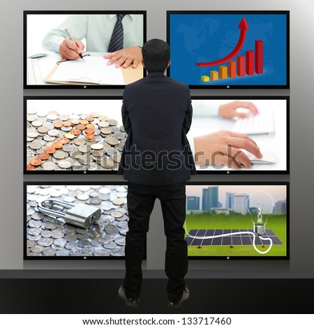 Businessman standing looking at the TV screen - stock photo