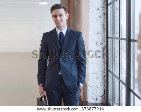 Businessman standing near office window. Manager director boss entrepreneur employer. - stock photo