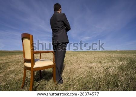 businessman standing next to a chair in outdoor looking to the field - stock photo