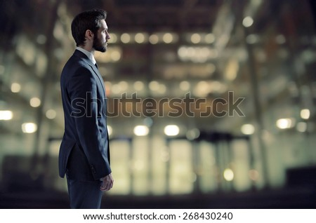 Businessman standing next to an apartment window - stock photo