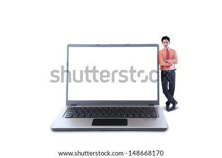 Businessman standing next to blank laptop , isolated on white