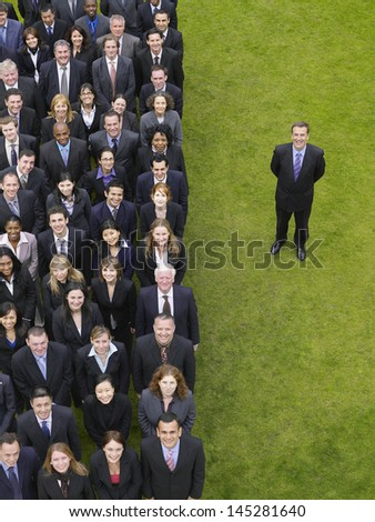Businessman standing next to large group of multiethnic businesspeople in row - stock photo