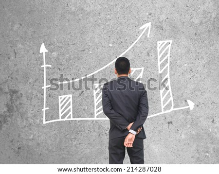 businessman standing of watching growing graph.