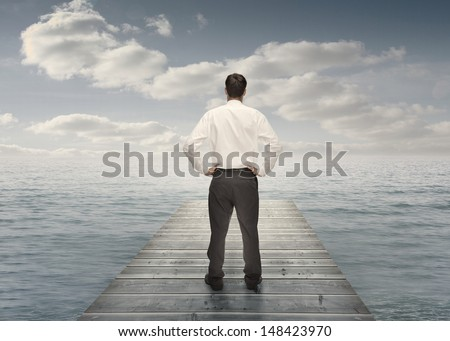 Businessman standing on a bridge with hands on hips and looking at the sea