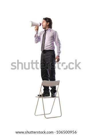 Businessman standing on a chair and screaming into a megaphone