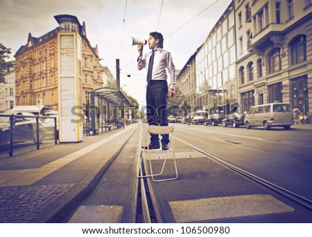 Businessman standing on a chair and screaming into a megaphone in the middle of a city street - stock photo