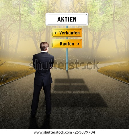 businessman standing on a crossroad, having to choose the right path what to do (with the words shares, sell and buy in German) - stock photo