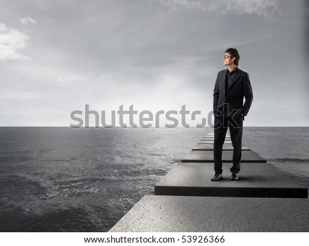 Businessman standing on a pad over the sea