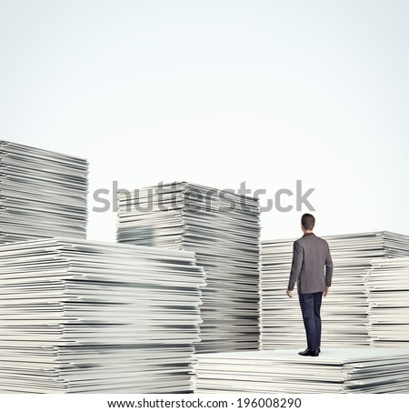Businessman standing on a pile of  documents - stock photo
