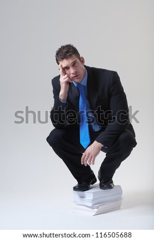 businessman standing on a pile of paper