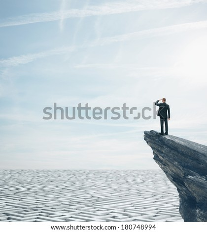 Businessman standing on a rock and looking at huge labyrinth - stock photo