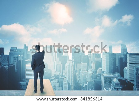 Businessman standing on a roof and looking at future city - stock photo