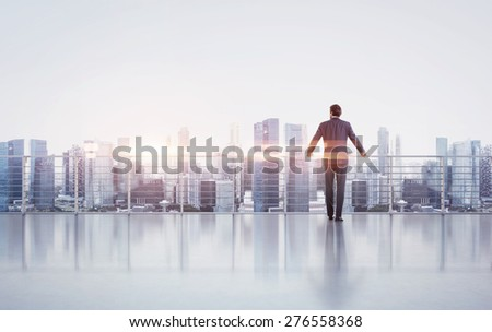 Businessman standing on a roof and looking at sunset - stock photo