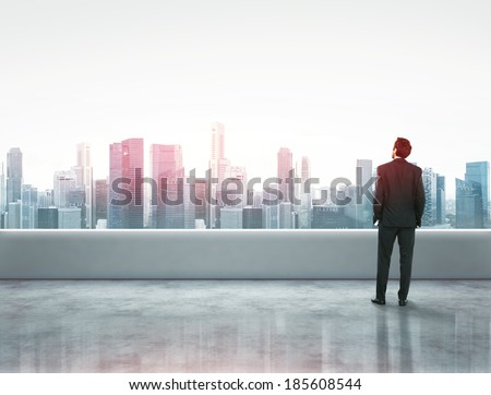 Businessman standing on a roof and looking city  - stock photo