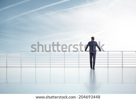 Businessman standing on a roof and looking sky - stock photo