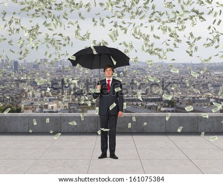 Businessman standing on a roof in the rain of money. - stock photo