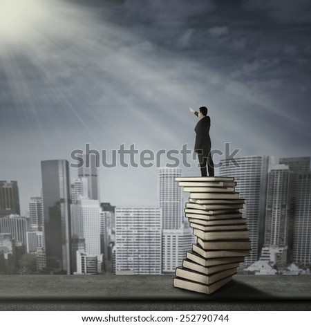 Businessman standing on a stack of books in the city - stock photo