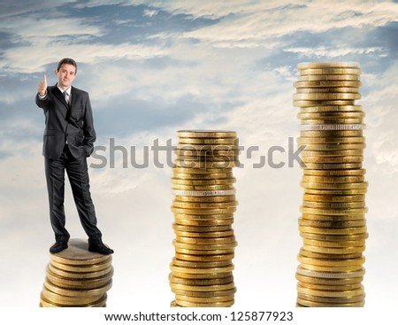 Businessman standing on a stack of money