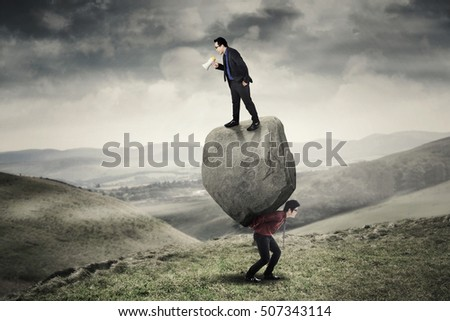 Businessman standing on a stone and shouting through a megaphone while his partner carrying the stone on the hill