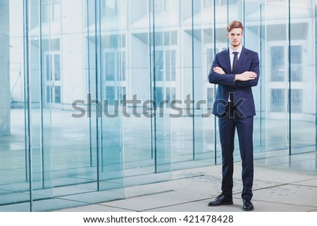 businessman standing on abstract business background, full body portrait - stock photo