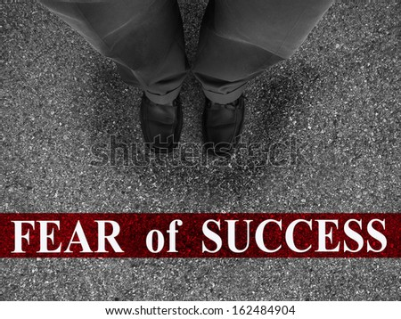 Businessman standing on asphalt starting line with word fear of success - stock photo