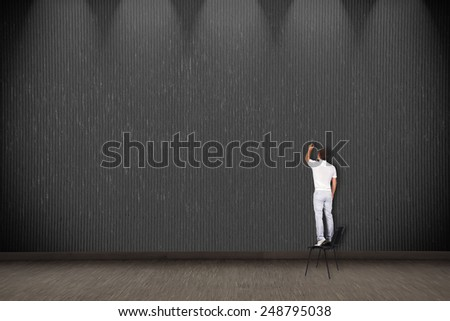businessman standing on chair and drawing on concrete wall - stock photo
