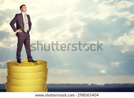 Businessman standing on coins stack and looking up - stock photo