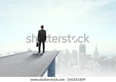 businessman standing on concrete bridge an looking at city - stock photo