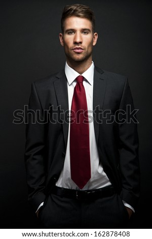 Businessman standing on dark gradient background - stock photo