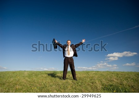 Businessman standing on green grass - arms outstretched with case, deep blou sky and white clouds - stock photo