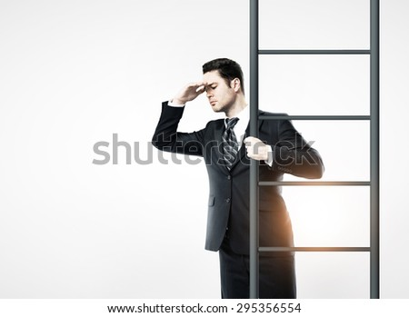 businessman standing on ladder and looking - stock photo