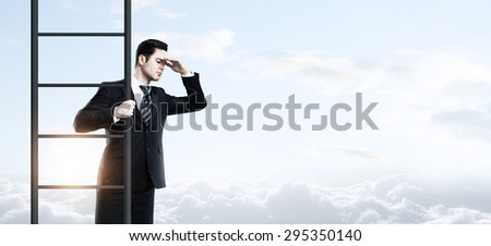 businessman standing on ladder and looking to sky
