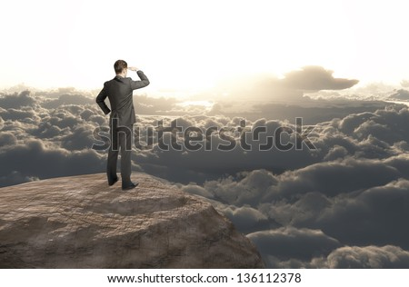 businessman standing on mountain and looking cloud
