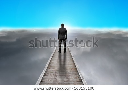 businessman standing on pier looking sunrise with dark clouds and blue sky