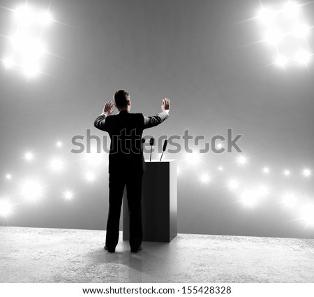 businessman standing on podium and closes on outbreaks - stock photo