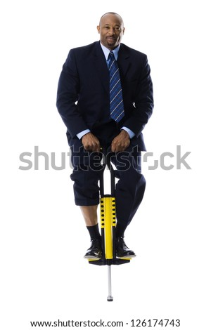 Businessman standing on pogo stick
