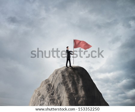 businessman standing on rock with red flag - stock photo