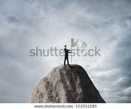 businessman standing on rock with white flag - stock photo