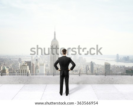 businessman standing on roof and looking on city - stock photo