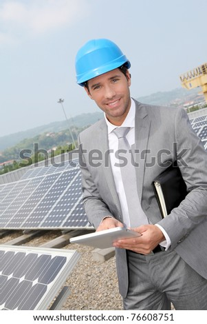 Businessman standing on solar panel installation - stock photo