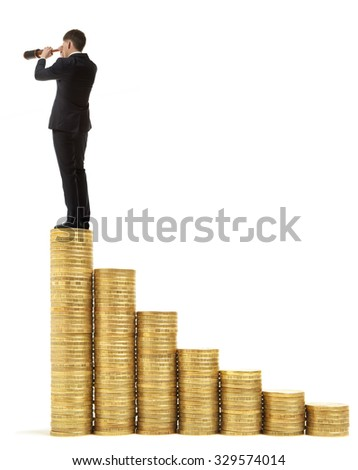 Businessman standing on stack of coins and looking through a telescope